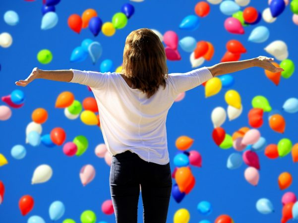Woman standing with her arms out in front of a sky filled with balloons