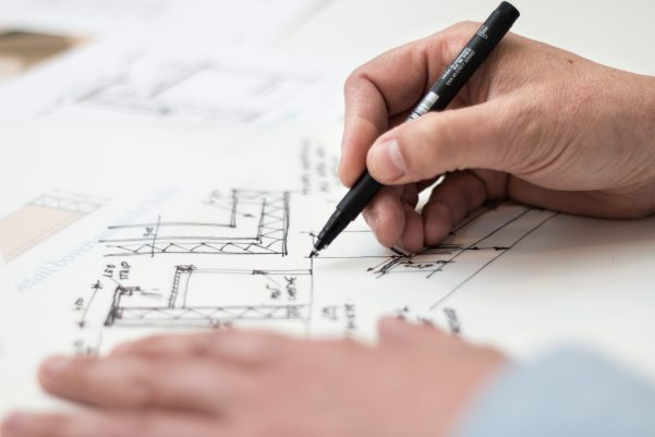Close-up of architect drawing a floor plan with a black marker on white paper