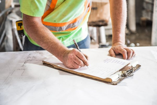 Health and Safety Officer carrying out a fire risk assessment with a pencil and clipboard on a table