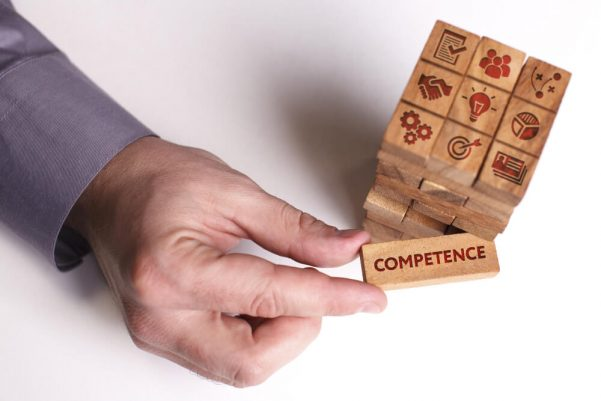 Block of wooden Jenga blocks with a hand pulling away a block marked with the word competence