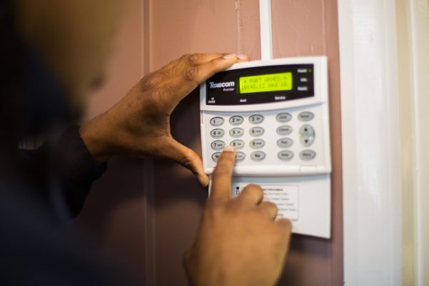 Close-up of an engineer's hands working on an intruder alarm panel
