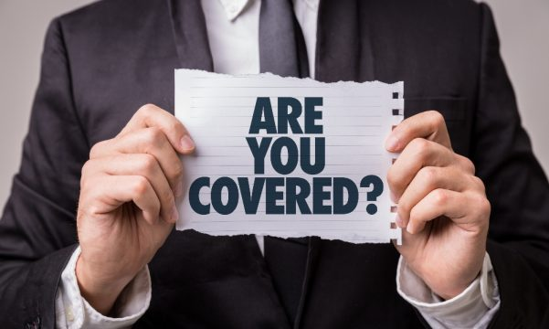 Man in a suit holding piece of paper saying 'are you covered?'