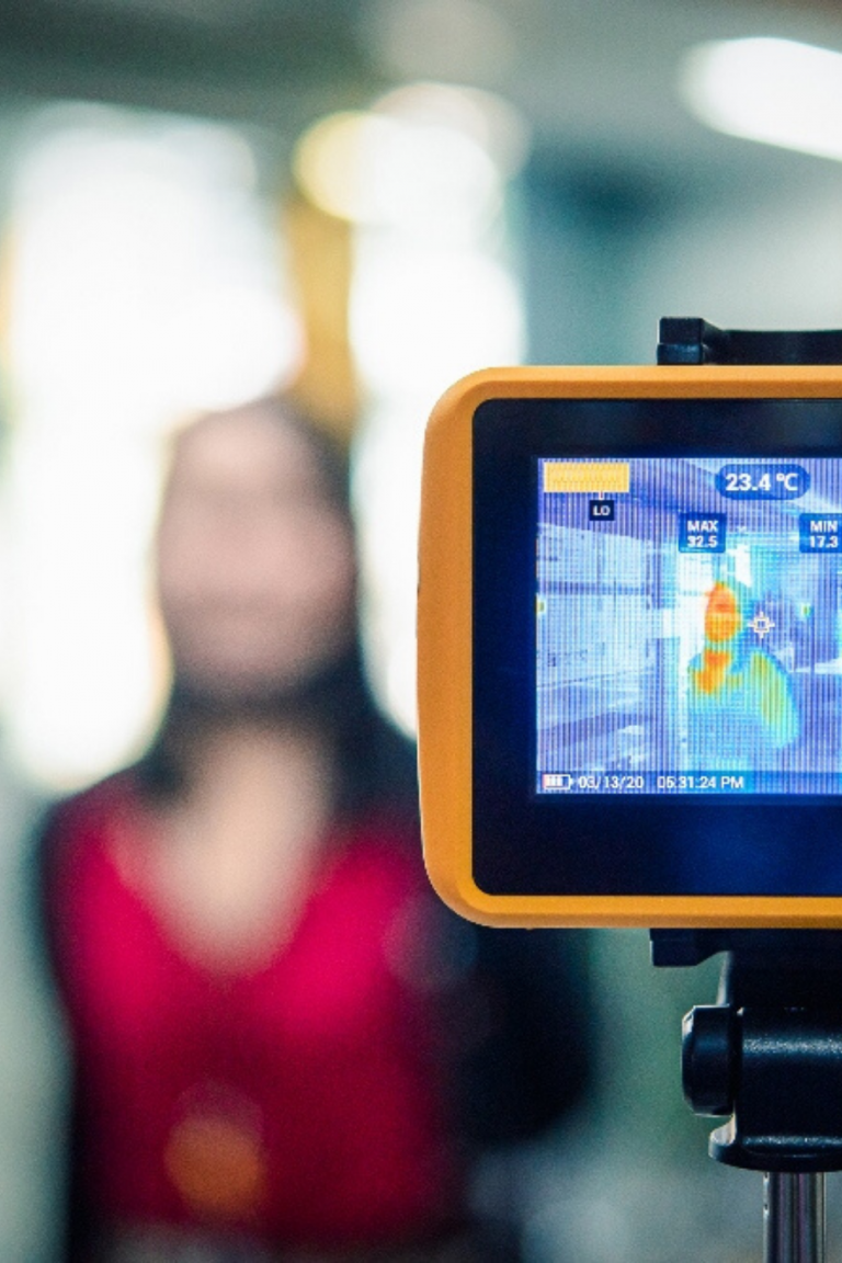 Thermal camera displaying temperature screening of an individual standing in front of the camera