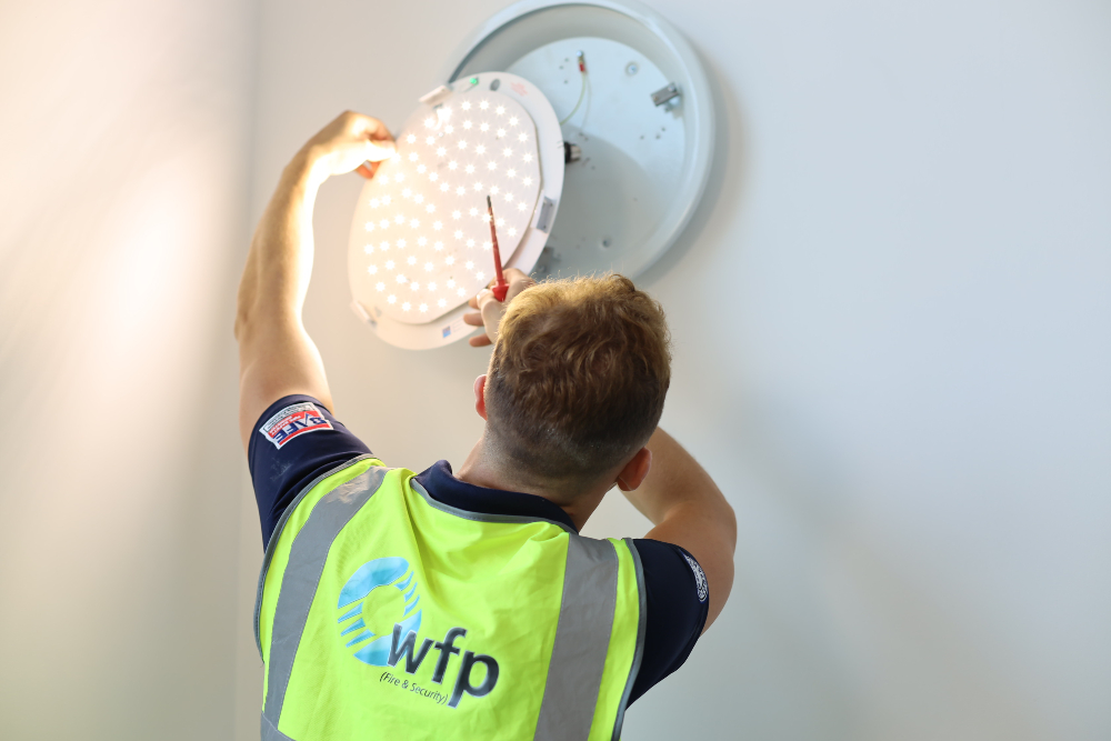 WFP Engineer installing a light wearing a high vis vest