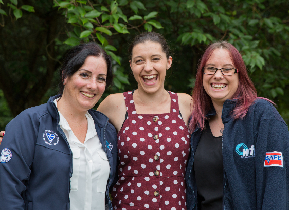 Three women standing together smiling