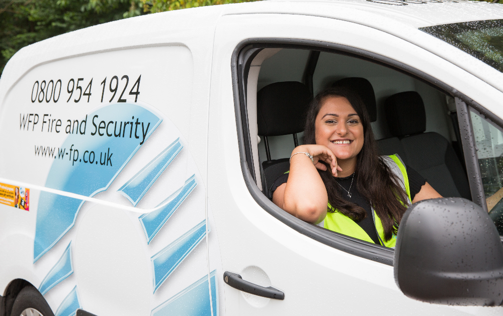 Woman in high vis vest smiling out of window in a van